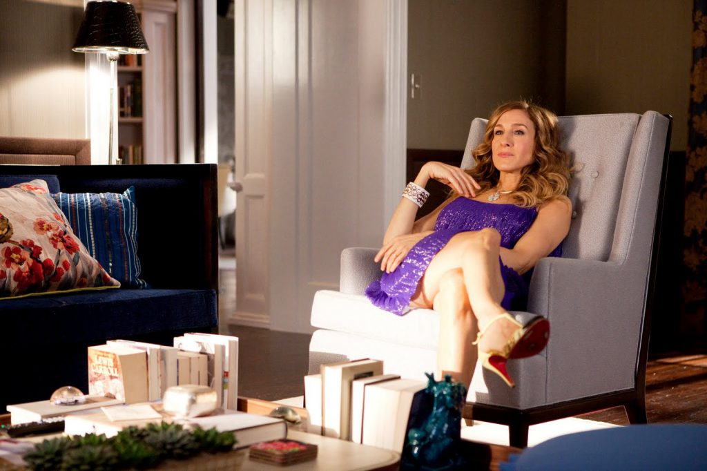 SATC 2 Set design inspired interior design ideas. Carrie and Big's living room. Carrie sitting in a vintage armchair.