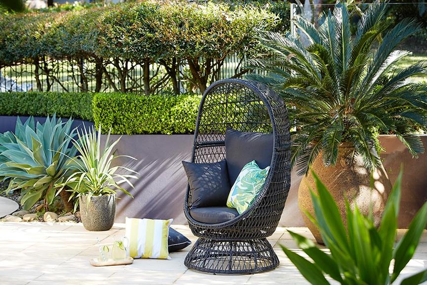 wicker egg chair in leafy garden